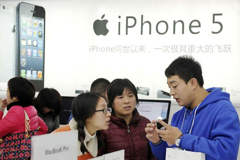 Customers check out iPhones last week at an Apple store in Dongyang, China. Photo: Associated Press