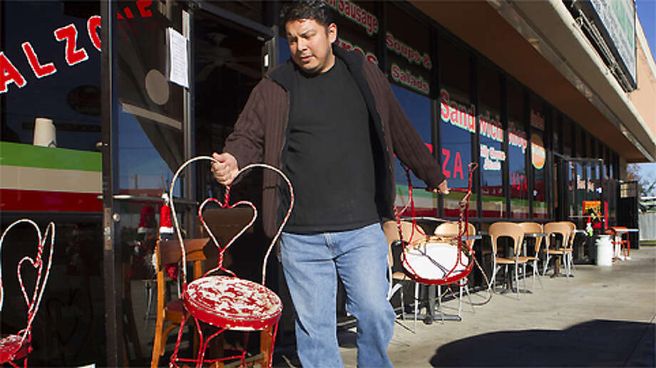 "Chicago Pizza and Italian Beef cashier Frank Perez prepares the outdoor seating on Airline Drive, Monday, Dec. 17, 2012, in Houston. Perez said that last week when the weather was cold, people don't sit outside. ""When the weather is nicer, we have more walk-in customers and people that sit outside,"" Perez said. ""When the weather is more cold, we get more deliveries."" Photo: Cody Duty, . / © 2012 Houston Chronicle"