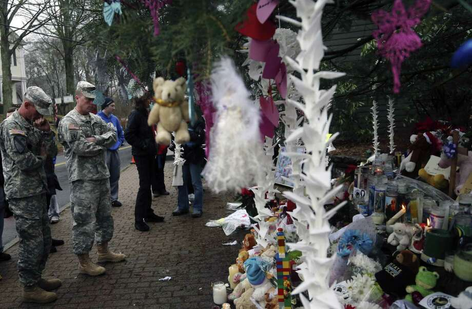 Soldiers pay their respects at one of the makeshift memorials for the Sandy Hook elementary shooting, Monday,Dec. 17, 2012 in Newtown, Conn. Authorities say a gunman killed his mother at their home and then opened fire inside the Sandy Hook Elementary School in Newtown, killing 26 people, including 20 children, before taking his own life, on Friday. (AP Photo/Mary Altaffer) Photo: Associated Press