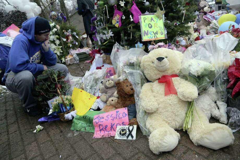 A]mourner pays his respects at one of the makeshift memorials for the Sandy Hook elementary shooting, Monday,Dec. 17, 2012 in Newtown, Conn. Authorities say a gunman killed his mother at their home and then opened fire inside the Sandy Hook Elementary School in Newtown, killing 26 people, including 20 children, before taking his own life, on Friday. (AP Photo/Mary Altaffer) Photo: Associated Press