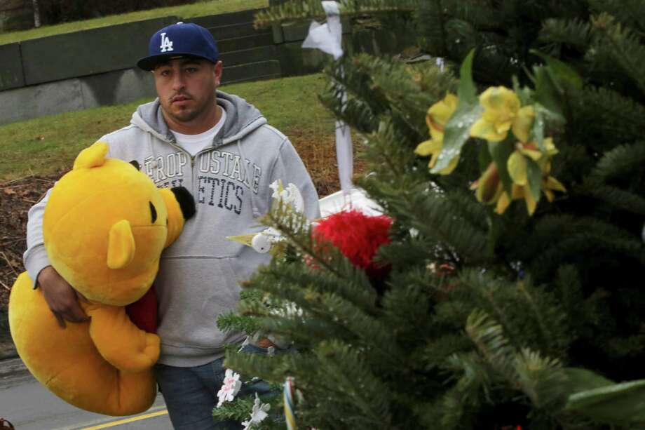 A mourner carries a giant Winnie the Pooh stuffed animal to place at one of the makeshift memorials for the Sandy Hook Elementary School shooting victims, Monday,Dec. 17, 2012 in Newtown, Conn. Authorities say gunman Adam Lanza killed his mother at their home on Friday and then opened fire inside the Sandy Hook Elementary School in Newtown, killing 26 people, including 20 children, before taking his own life. (AP Photo/Mary Altaffer) Photo: Associated Press