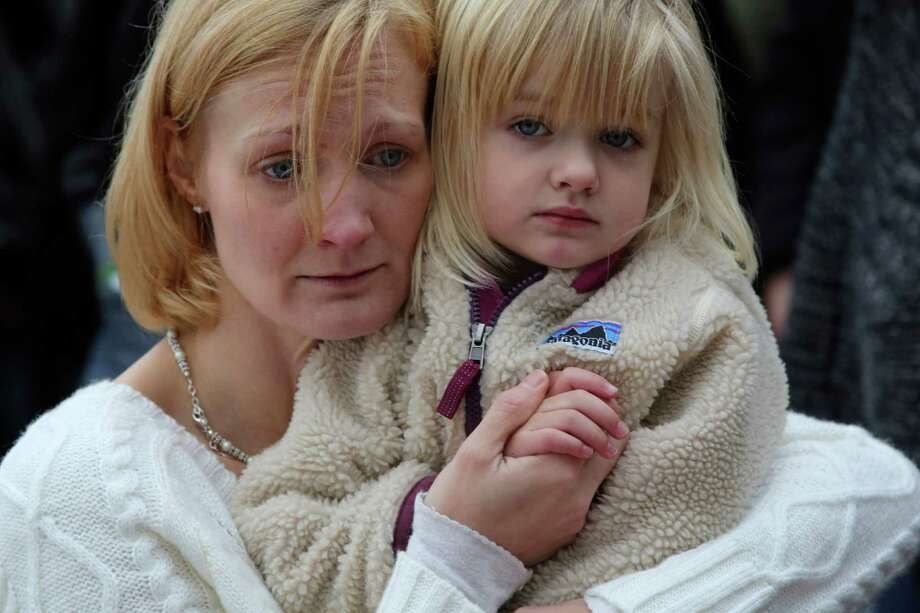 Barbara Wells, of Shelton, Conn., holds her daughter Olivia, 3, as she pays her respects at one of the makeshift memorials for the Sandy Hook Elementary School shooting victims, Monday, Dec. 17, 2012 in Newtown, Conn. Authorities say a gunman killed his mother at their home and then opened fire inside the Sandy Hook Elementary School in Newtown, killing 26 people, including 20 children, before taking his own life, on Friday.(AP Photo/Mary Altaffer) Photo: Associated Press
