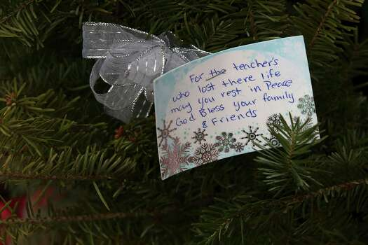 A note is left at one of the makeshift memorials for the Sandy Hook Elementary School shooting victims, Monday, Dec. 17, 2012 in Newtown, Conn. Authorities say gunman Adam Lanza killed his mother at their home on Friday and then opened fire inside the Sandy Hook Elementary School in Newtown, killing 26 people, including 20 children, before taking his own life. (AP Photo/Mary Altaffer) Photo: Associated Press