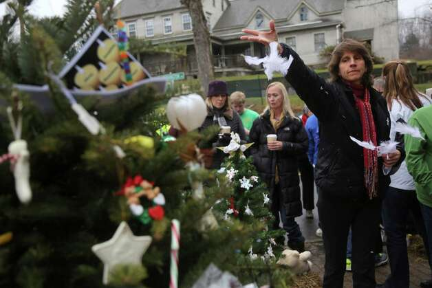 A mourner throws feathers at one of the makeshift memorials for the Sandy Hook elementary shooting, Monday,Dec. 17, 2012 in Newtown, Conn. Authorities say gunman Adam Lanza killed his mother at their home on Friday and then opened fire inside the Sandy Hook Elementary School in Newtown, killing 26 people, including 20 children, before taking his own life. (AP Photo/Mary Altaffer) Photo: Associated Press