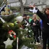 A mourner throws feathers at one of the makeshift memorials for the Sandy Hook elementary shooting, Monday,Dec. 17, 2012 in Newtown, Conn. Authorities say gunman Adam Lanza killed his mother at their home on Friday and then opened fire inside the Sandy Hook Elementary School in Newtown, killing 26 people, including 20 children, before taking his own life. (AP Photo/Mary Altaffer)