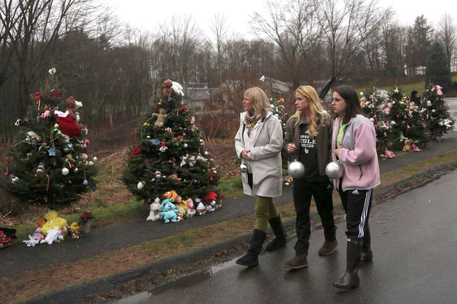 Mourners carry ornaments to decorate the Christmas trees at one of the makeshift memorials for the Sandy Hook Elementary School shooting victims, Monday,Dec. 17, 2012 in Newtown, Conn. Authorities say gunman Adam Lanza killed his mother at their home on Friday and then opened fire inside the Sandy Hook Elementary School in Newtown, killing 26 people, including 20 children, before taking his own life. (AP Photo/Mary Altaffer) Photo: Associated Press