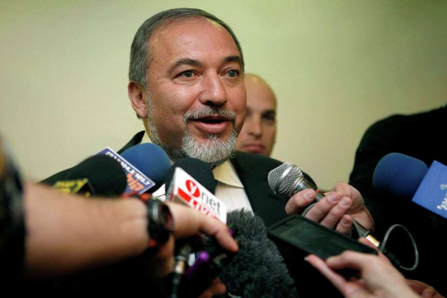 Israeli Foreign Minister Avigdor Lieberman speaks to journalists as he arrives to the weekly cabinet meeting at the prime minister's office in Jerusalem, Sunday, Dec. 16, 2012. Lieberman has tendered his official resignation over fraud and breach of trust charges filed against him. (AP Photo/Gali Tibbon, Pool) Photo: Gali Tibbon, STR / AFP