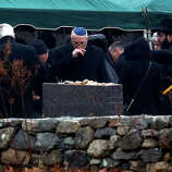 A man, center, reacts while others shovel dirt onto the grave of Noah Pozner, a six-year-old killed in the Sandy Hook Elementary School shooting, was laid to rest at B'nai Israel Cemetery, Monday, Dec. 17, 2012, in Monroe, Conn. Authorities say gunman Adam Lanza killed his mother at their home on Friday and then opened fire inside the Sandy Hook Elementary School in Newtown, killing 26 people, including 20 children, before taking his own life.