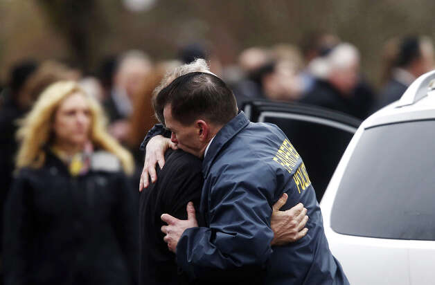 Fairfield police chief Gary MacNamara embraces a relative of Noah Pozner after a funeral service for the 6-year-old shooting victim, Monday, Dec. 17, 2012, in Fairfield, Conn.  Pozner was killed when a gunman walked into Sandy Hook Elementary School in Newtown Friday and opened fire, killing 26 people, including 20 children. Photo: Jason DeCrow, AP / AP2012