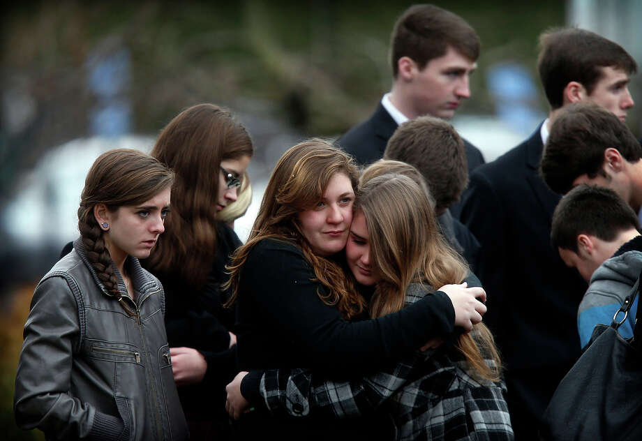 Mourners comfort one another as they leave a funeral service for 6-year-old Noah Pozner, Monday, Dec. 17, 2012, in Fairfield, Conn.  Pozner was killed when a gunman walked into Sandy Hook Elementary School in Newtown Friday and opened fire, killing 26 people, including 20 children. Photo: Jason DeCrow, AP / AP2012