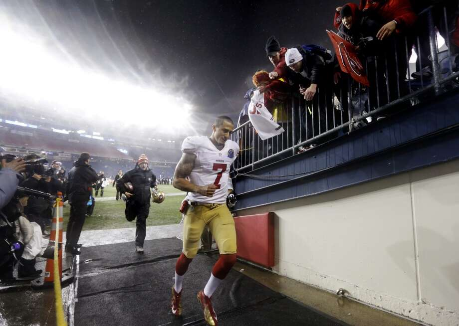 San Francisco 49ers quarterback Colin Kaepernick (7) runs past fans as he leaves the field after defeating the New England Patriots 41-34 in an NFL football game in Foxborough, Mass., Monday, Dec. 17, 2012.  (Elise Amendola / Associated Press)