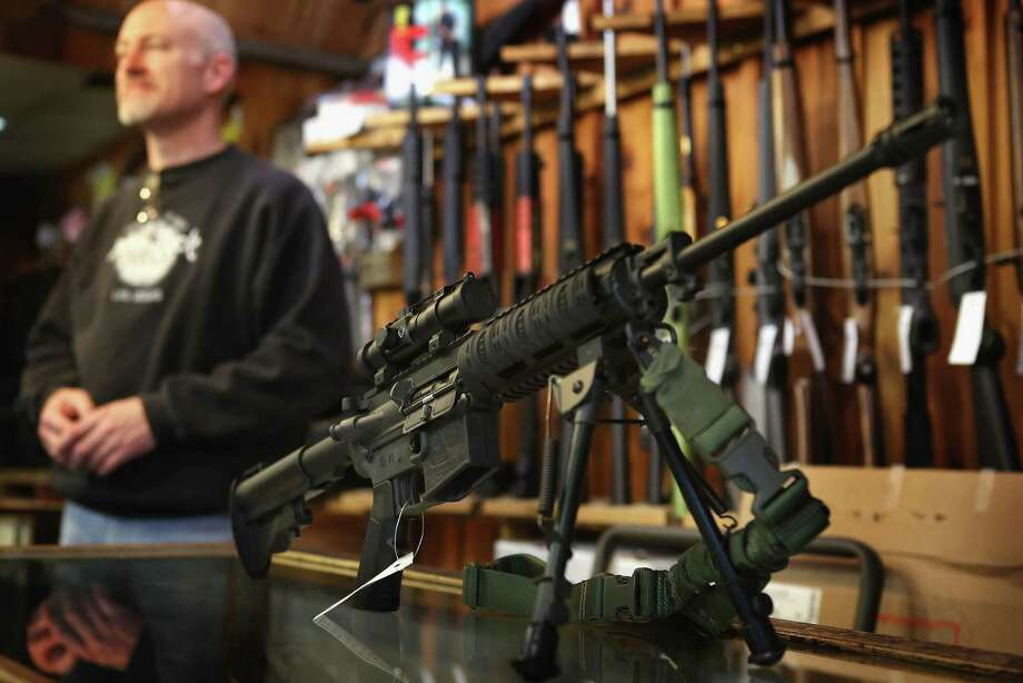 TINLEY PARK, IL - DECEMBER 17:  An AR-15 style rifle sits on the counter by Craig Marshall as he assists a customer at Freddie Bear Sports sporting goods store on December 17, 2012 in Tinley Park, Illinois.  Americans purchased a record number of guns in 2012 and gun makers have reported a record high in demand. Firearm sales have surged recently as speculation of stricter gun laws and a re-instatement of the assault weapons ban following the mass school shooting in Connecticut . Photo: Scott Olson, Getty Images / 2012 Getty Images