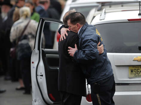 Fairfield Police Chief Gary McNamara, right, hugs a family member outside the funeral for her six year-old son Noah Pozner, killed in the mass shooting at Sandy Hook Elementary School in Newtown, at the Abraham L. Green Funeral home in Fairfield on Monday, December 17, 2012. Photo: Brian A. Pounds / Connecticut Post