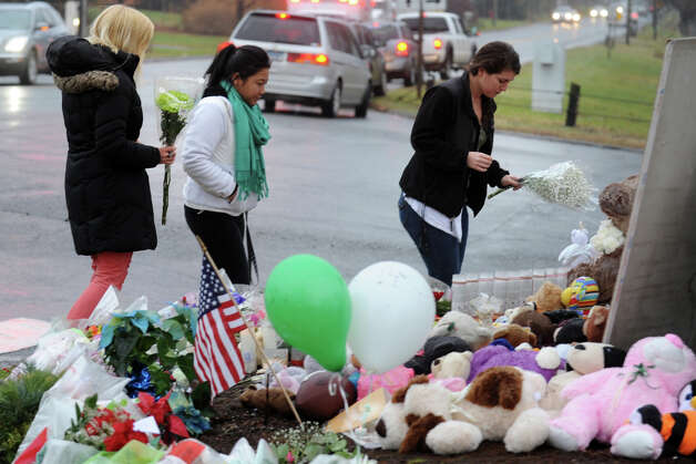 A group of girls stop to place flowers on a memrial set up on The PLeasance, a town park on Main Street, in Newtown, Conn., Dec. 17th, 2012. Monday was the first day of funerals for victims of the Sandy Hook Elementary School shootings last Friday. Photo: Ned Gerard / Connecticut Post