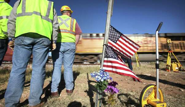 A Union Pacific frieght train speeds by around 65 mph where crime scene technicians and lawyers gather evidence at the scene of the Nov. 15 train wreck where four died while riding on a parade float that was struck by a freight train, in Midland, TX, Monday, Dec. 17, 2012. Photo: Bob Owen, San Antonio Express-News / © 2012 San Antonio Express-News