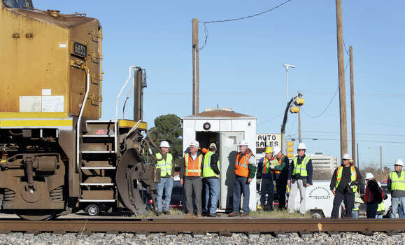A slow moving train passes by lawyers and data gathering technicians at the scene of the fatal train wreck where four were killed while riding on a parade float that was struck by a freight train a month ago, in Midland, TX, Monday, Dec. 17, 2012. Photo: Bob Owen, San Antonio Express-News / © 2012 San Antonio Express-News