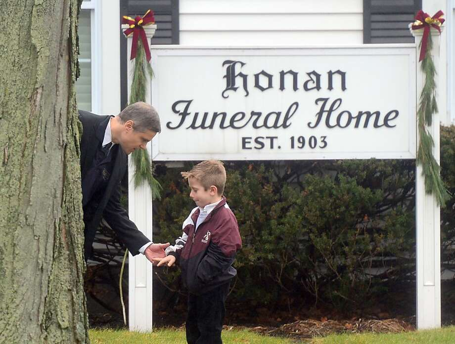 A man talks to his son before Monday's funeral for Jack Pinto, 6, a victim of the school massacre in Newtown, Conn. Photo: Emmanuel Dunand, AFP/Getty Images