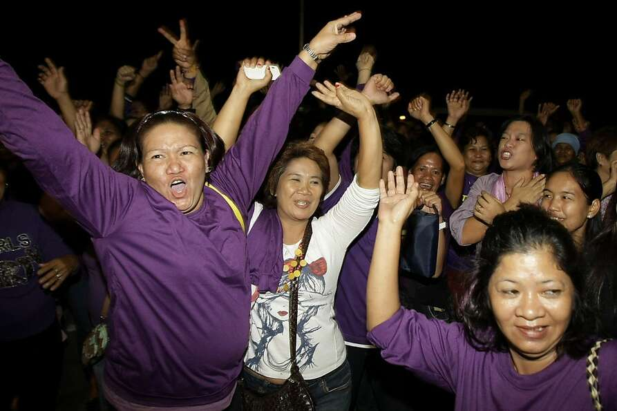 Filipino women celebrate as Philippine legislators pass a landmark law that would provide government