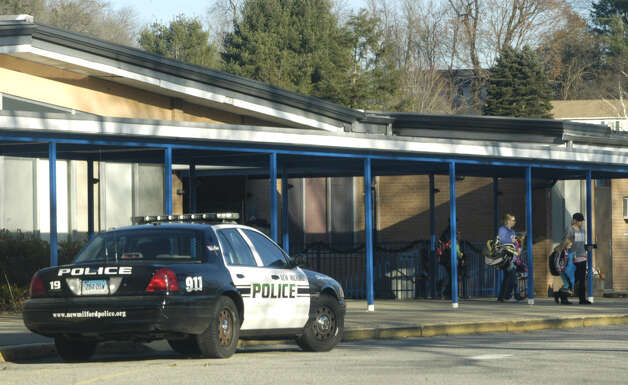 New Milford police were on duty at all of the school district's six schools, including Hill and Plain, above, as parents met their children Friday afternoon, Dec. 14, 2012 following a lockdown of the schools, The lockdown had been prompted by the mass shooting earlier that day at Sandy Hook Elementary School in Newtown. Photo: Norm Cummings
