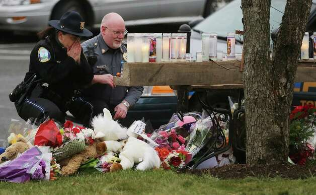 Newtown Police officers pay their respects at a makeshift memorial outside St. Rose of Lima Roman Catholic Church during the first day of Sunday services following the mass shooting at Sandy Hook Elementary School on December 16, 2012 in Newtown, Connecticut.  Twenty six people were shot dead, including twenty children, after a gunman identified as Adam Lanza in news reports opened fire in the school. Lanza also reportedly had committed suicide at the scene. Photo: Mario Tama, Photo By Mario Tama/Getty Images / Getty Images