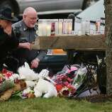 Newtown Police officers pay their respects at a makeshift memorial outside St. Rose of Lima Roman Catholic Church during the first day of Sunday services following the mass shooting at Sandy Hook Elementary School on December 16, 2012 in Newtown, Connecticut.  Twenty six people were shot dead, including twenty children, after a gunman identified as Adam Lanza in news reports opened fire in the school. Lanza also reportedly had committed suicide at the scene.