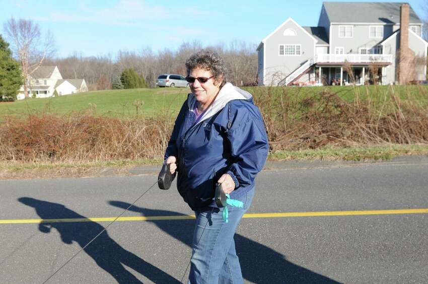 Marsha Moskowitz, a school bus driver who lives near the Lanza home in Newtown Conn., walks her dogs Saturday afternoon Dec. 15, 2012, on Bennetts Bridge Road in Newtown. Adam Lanza, age 20, was identified by authorities as the killer who fatally shot his mother in her home before gunning down 20 children and 6 adults at Sandy Hook Elementary School in Newtown Conn. (Will Waldron / Times Union)