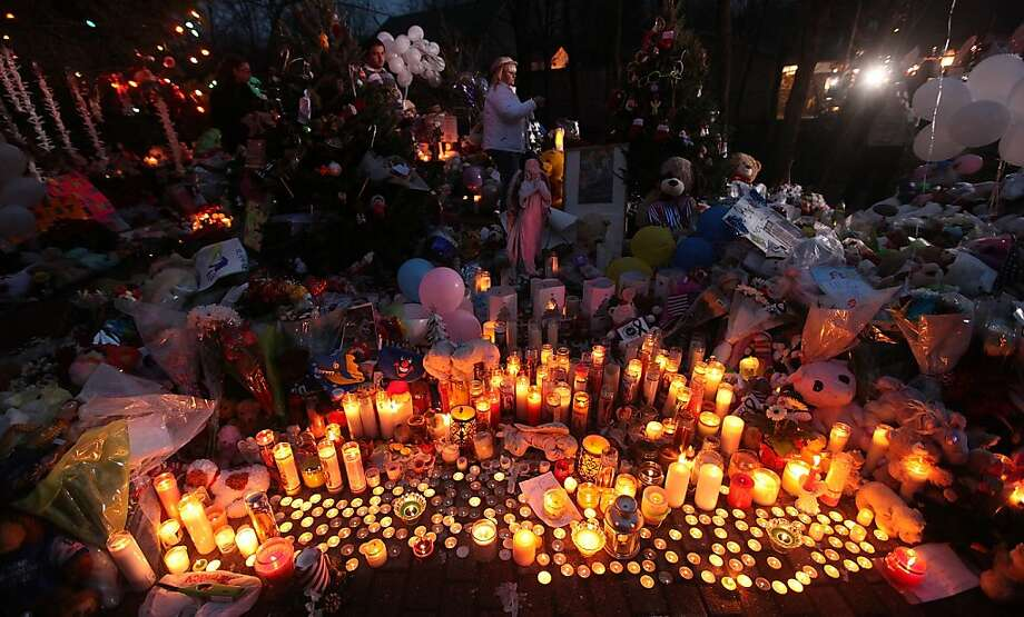 Candles for the victims of the Newtown shooting burn among other mementos outside Sandy Hook Elementary School. Photo: Mario Tama, Getty Images