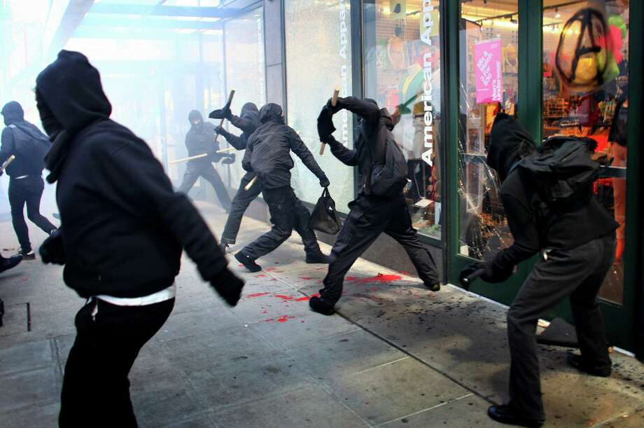 May 1, 2012 — Black-clad protesters break windows on downtown businesses —including American Apparel and NikeTown— during a May Day rally and march. A group of a few dozen protestors caused mayhem in downtown Seattle by smashing windows and vandalizing businesses, cars and the downtown federal courthouse. Investigations later pointed to many of the agitators coming from out of town, with a plan to wreak havoc on Seattle as an expression of their frustration with the government and consumer culture. Story here. Photo: JOSHUA TRUJILLO / SEATTLEPI.COM