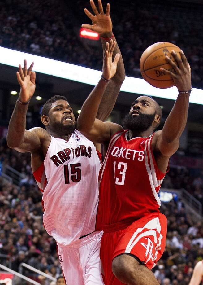 Rockets guard James Harden, right, drives to the basket against Raptors forward Amir Johnson. (Aaron Vincent Elkaim / Associated Press)