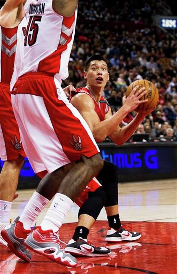 Rockets guard Jeremy Lin is pressured by Raptors forward Amir Johnson (Aaron Vincent Elkaim / Associated Press) Photo: Aaron Vincent Elkaim, AP / The Canadian Press