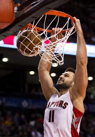 Raptors forward Linas Kleiza dunks the ball against the Rockets. (Aaron Vincent Elkaim / Associated Press)