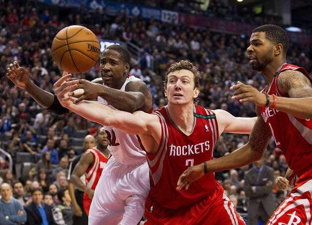 Rockets center Omer Asik reaches for the ball against Raptors center Ed Davis. (Aaron Vincent Elkaim / Associated Press)