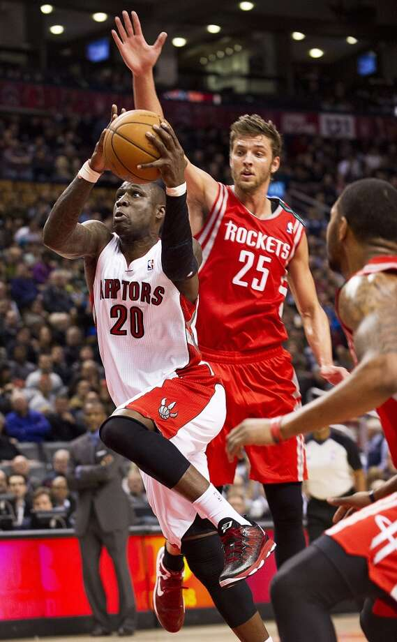 Raptors forward Michael Pietrus goes to the basket past Rockets forward Chandler Parsons. (Aaron Vincent Elkaim / Associated Press)