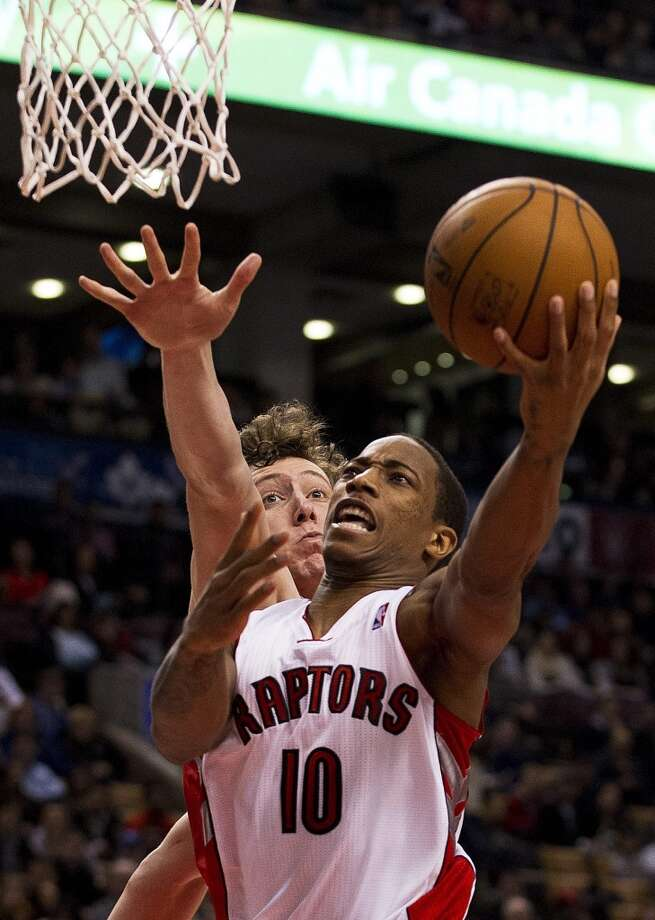 Raptors guard DeMar DeRozan attempts a shot over Rockets center Omer Asik. (Aaron Vincent Elkaim / Associated Press)