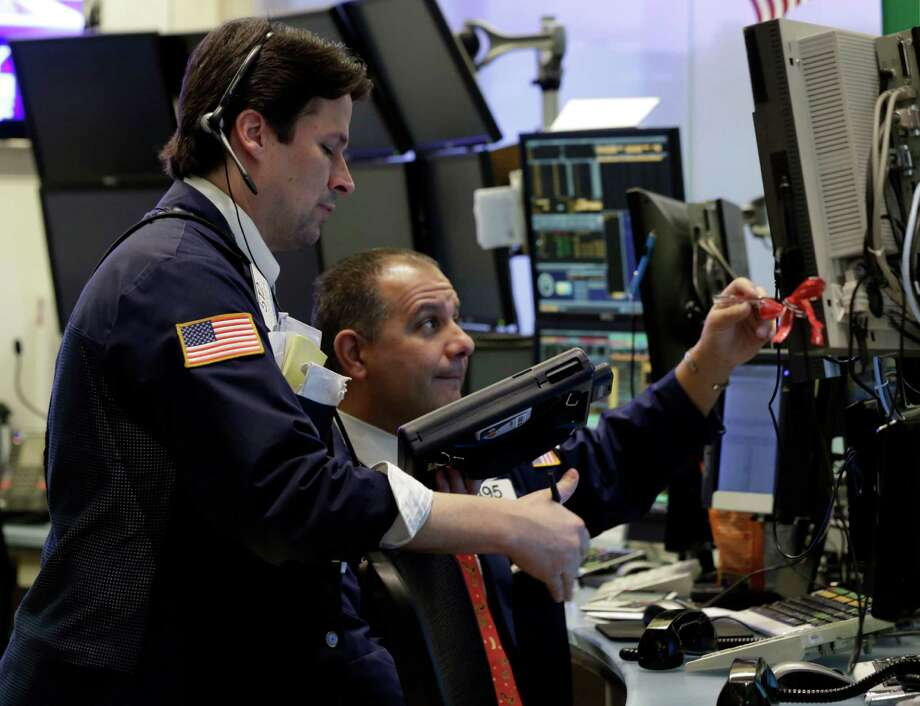 "In this Friday, Dec. 14, 2012,  photo, Traders Patrick McKeon, left, and Joel Lucchese work on the floor of the New York Stock Exchange. Stocks rose modestly Monday, Dec. 17, 2012, on Wall Street. Investors were encouraged by signs of progress in talks to avoid the ""fiscal cliff"" of tax increases and government spending cuts set to take effect in two weeks and a prediction of steady economic growth next year. (AP Photo/Richard Drew) Photo: Richard Drew"