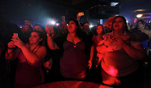Fans watch Jenni Rivera impersonator Odalis Aranjin, 33, (not pictured) perform Friday Dec. 14, 2012 at El Fuerte. Photo: Edward A. Ornelas, San Antonio Express-News / © 2012 San Antonio Express-News