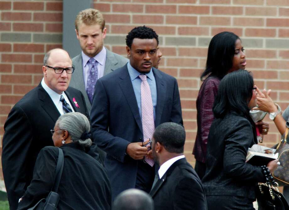 ADDS NAME OF BRANDON CARR - Kansas City Chiefs general manager Scott Pioli, left, and others leave the funeral service for Kasandra Perkins at the St. James Missionary Baptist Church on Saturday, Dec. 8, 2012, in Austin, Texas. Perkins was shot and killed Dec. 1 by her boyfriend Jovan Belcher, a Chiefs football player, Belcher later killed himself. Dallas Cowboys cornerback Brandon Carr, center, knew Belcher and Perkins well. (AP Photo/Jack Plunkett) Photo: Jack Plunkett, FRE / FR59553 AP