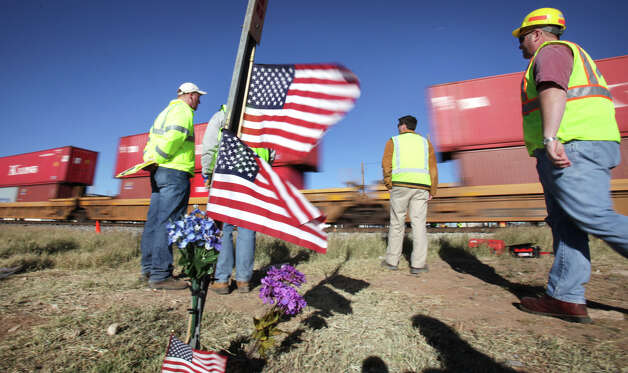 Flags are set up where four died while riding on a parade float, Nov, 15, that was struck by a freight train, in Midland, TX. A frieght train speeds by around 65 mph where crime scene technicians and lawyers gather evidence at the scene, Monday, Dec. 17, 2012. Photo: Bob Owen, San Antonio Express-News / © 2012 San Antonio Express-News