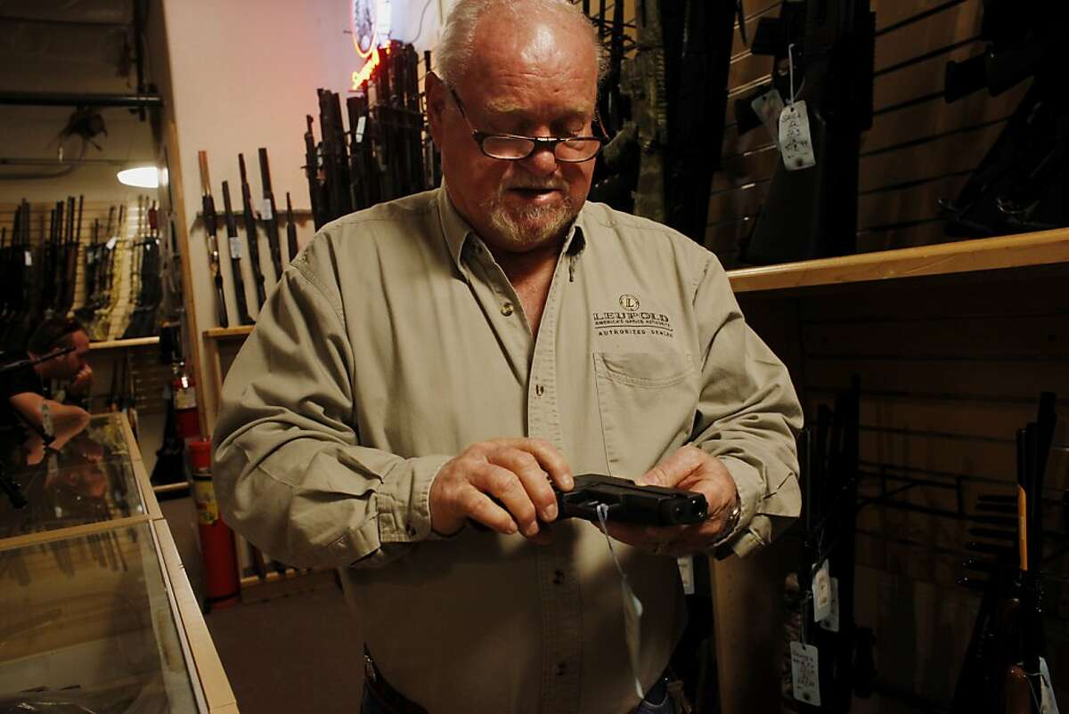 Bob Morgan, owner of the Guns, Fishing and Other Stuff, handles a pistol similar to the ones Adan Lanza used in the Connecticut killing, Monday Dec. 17, 2012, in Vacaville, Calif.