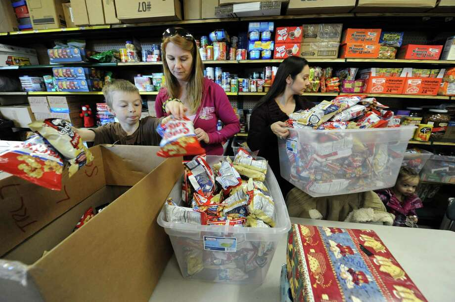 From left, Volunteers J.J. Adriance, 11, Wanda Closson and Erika Adriance, all of Ballston Spa, help package boxes at Operation Adopt a Soldier to ship to soldiers serving overseas on Thursday Dec. 13, 2012 in Wilton, N.Y.  (Lori Van Buren / Times Union) Photo: Lori Van Buren