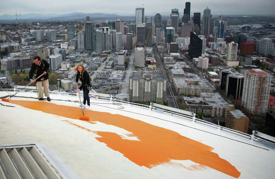 """April 17, 2012— Jeff Wright and his daughter Mauren Wright, 15, begin painting the roof of the Space Needle its original """"Galaxy Gold."""" Jeff Wright's father Howard S. Wright built the Space Needle for the Worlds Fair. In 2012 the icon was returned to its original color as part of the celebration of the 50th anniversary of the Needle and the Seattle Center. Story here. Photo: JOSHUA TRUJILLO / SEATTLEPI.COM"""