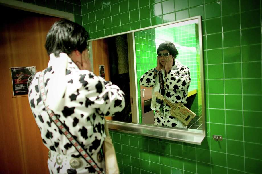 "January 14, 2012 — ""Elvince,"" aka Vince Hill of Bellingham, attaches his sideburns in the men's restroom during the ""Seattle Invitationals"" Elvis Tribute Artist competition at Seattle's EMP. To commemorate the 50th anniversary of the Seattle World's Fair, Elvis returned to the Seattle Center in the form of the impersonator competition. More here. Photo: JOSHUA TRUJILLO / SEATTLEPI.COM"