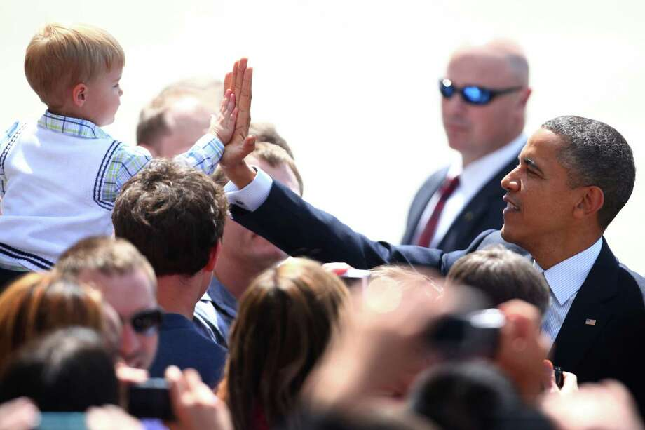 May 10, 2012— U.S. President Barack Obama high-fives a young supporter as Air Force One lands at Boeing Field during one of his many fund-raising visits to the Seattle area. The president attend two fund-raisers during the visit. Photo: JOSHUA TRUJILLO / SEATTLEPI.COM