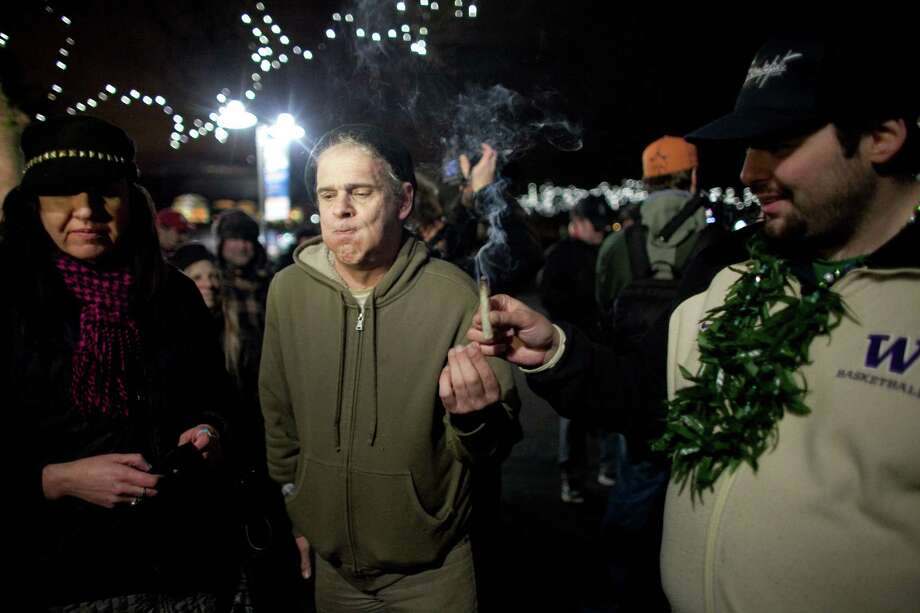 "December 6, 2012 — John, center, passes around a joint during a ""stash mob"" at Seattle's International Fountain. Recreational use of marijuana was legalized by voters in Washington State and people celebrated by smoking publicly at Seattle, something prohibited by the new law. Photo: JOSHUA TRUJILLO / SEATTLEPI.COM"