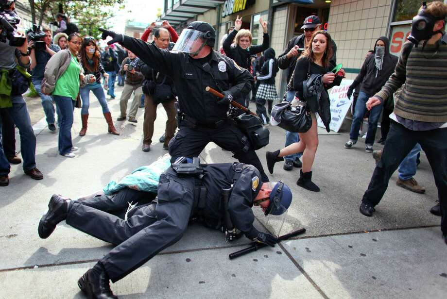 May 1, 2012— Officers arrest a man that threw a glass jar and hit an officer in his face shield during a May Day rally in downtown Seattle. The rally turned violent when black-clad protesters smashed windows and threw objects at police. Police responded with pepper spray and seized sticks and other potential weapons from the protesters. Photo: JOSHUA TRUJILLO / SEATTLEPI.COM
