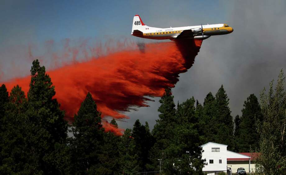 August 14, 2012 — A plane drops retardant to create a fire break at the Sunlight Waters housing development as the Taylor Bridge wildfire advances on the community near Cle Elum. Washington had a devastating fire season in 2012. The Taylor Bridge fire destroyed 61 homes as it burned across range land and forest. Story here. Photo: JOSHUA TRUJILLO / SEATTLEPI.COM