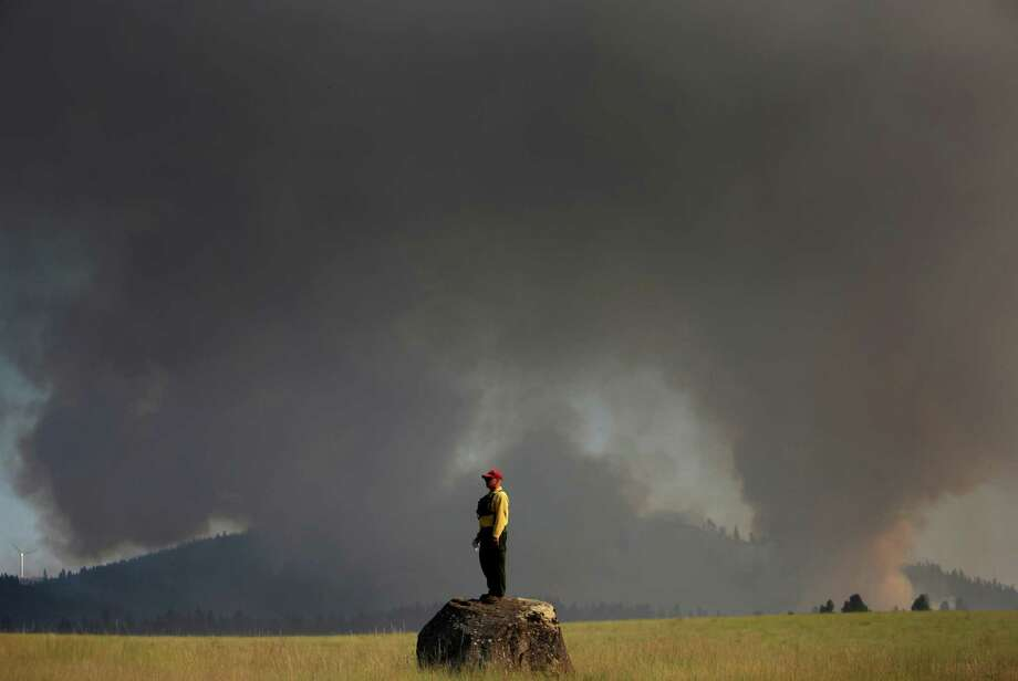 August 15, 2012— Marcus Johns, with the Department of Natural Resources, watches as the Taylor Bridge Fire burns on the south side of Highway 970 near Swauk Prairie Road near Cle Elum. The Taylor Bridge Fire forced hundreds to evacuate and burned 61 homes. Photo: JOSHUA TRUJILLO / SEATTLEPI.COM