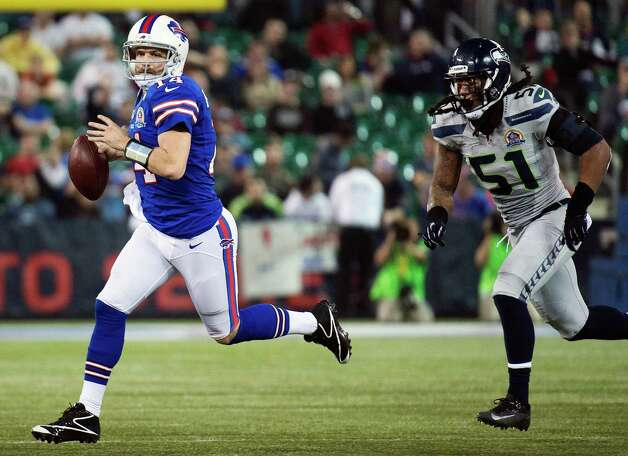 Buffalo Bills quarterback Ryan Fitzpatrick (14) looks for a pass as he is chased down by Seattle Seahawks defensive end Bruce Irvin (51) during the second half of an NFL football game, Sunday, Dec. 16, 2012, in Toronto. The Seahawks won 50-17. (AP Photo/The Canadian Press, Nathan Denette) Photo: Nathan Denette