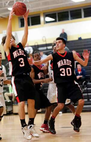 Fairfield Warde high school's Mike Pehota (left) puls down a rebound in a boys basketball game against Trumbull high school played at Trumbull high school, Trumbull, CT on Monday December 17th, 2012. At right is Fairfield Warde high school's Nick Cotto. Photo: Mark Conrad / Connecticut Post Freelance