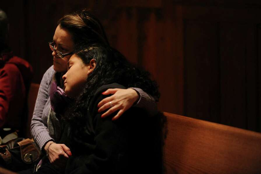 A mother and daughter listening to the prayers at memorial and healing Mass for the shooting victims